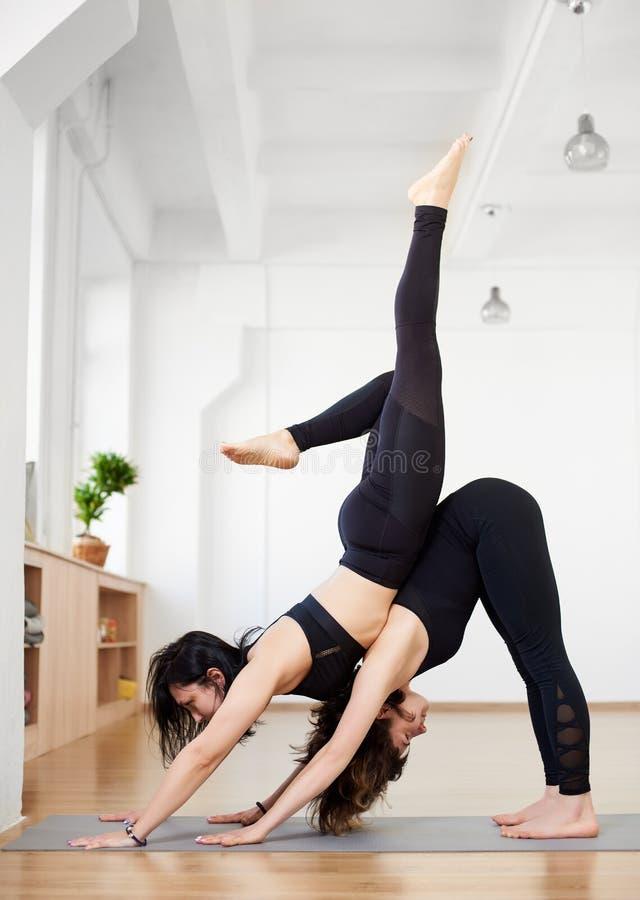Женский партнер в красивом представлении йоги Друзья в черных tracksuits делая протягивающ тренировку в студии йоги r стоковые фотографии rf