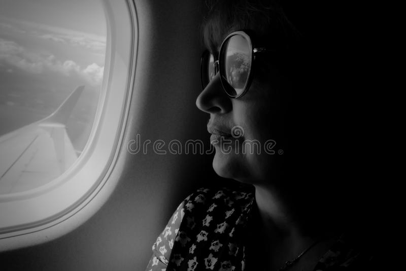 Женский пассажир сидит окном самолета Крыло  стоковые фото