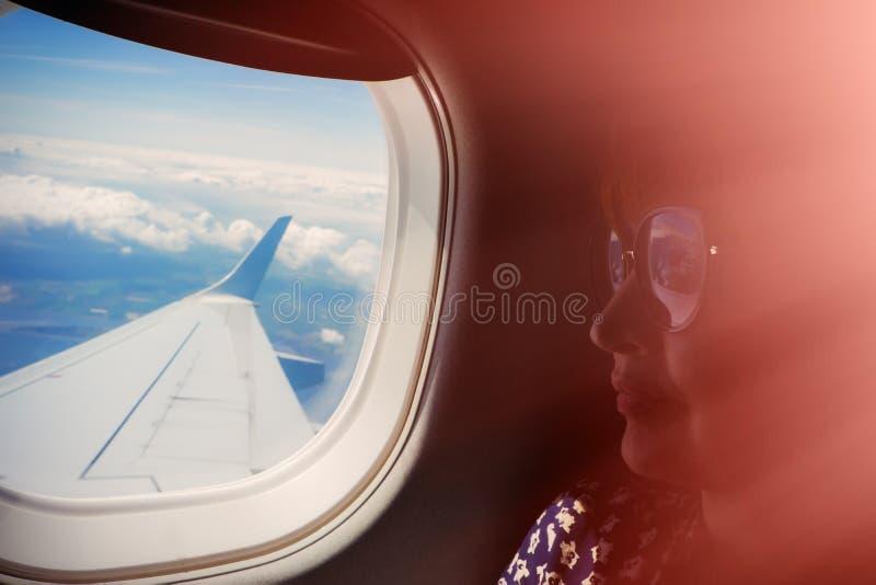 Женский пассажир сидит окном самолета Крыло  стоковое фото rf