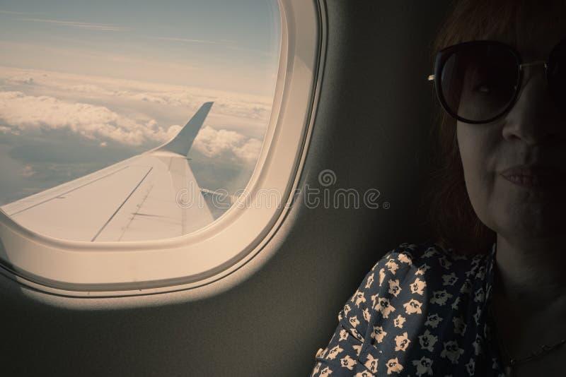 Женский пассажир сидит окном самолета Крыло  стоковые фотографии rf