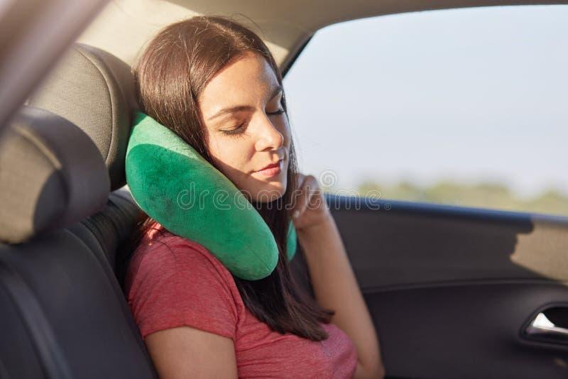 Женский пассажир спит в автомобиле пока езды на дальнем расстоянии, подушке польз малой как имеет боль в шеи, принимает ворсину,  стоковое фото