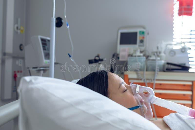 Женский пациент отдыхая в кровати в палате на больнице стоковые фотографии rf
