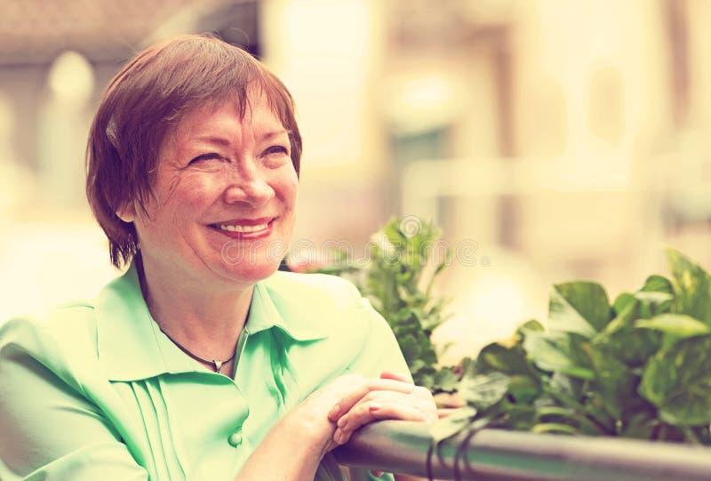 Женский пенсионер отдыхая на балконе стоковое изображение rf
