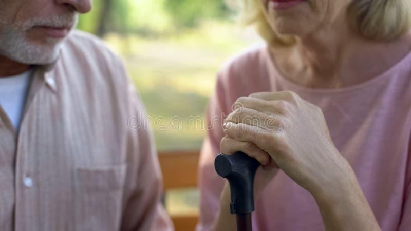 Женский пенсионер полагаясь на идя ручке, поддержке супруга, инвалидности старости стоковая фотография