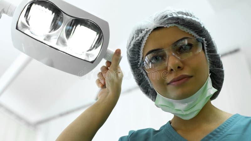 Женский пластический хирург регулируя света перед резекцией моли, пластической хирургией стоковые изображения