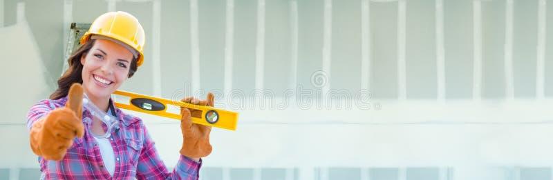 Женский подрядчик нося трудную шляпу против предпосылки знамени гипсокартона с лестницей стоковое фото