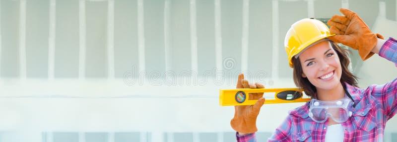 Женский подрядчик нося трудную шляпу против предпосылки знамени гипсокартона с лестницей стоковые изображения rf