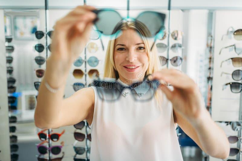 Женский покупатель выбирает солнечные очки в магазине оптики стоковые фотографии rf