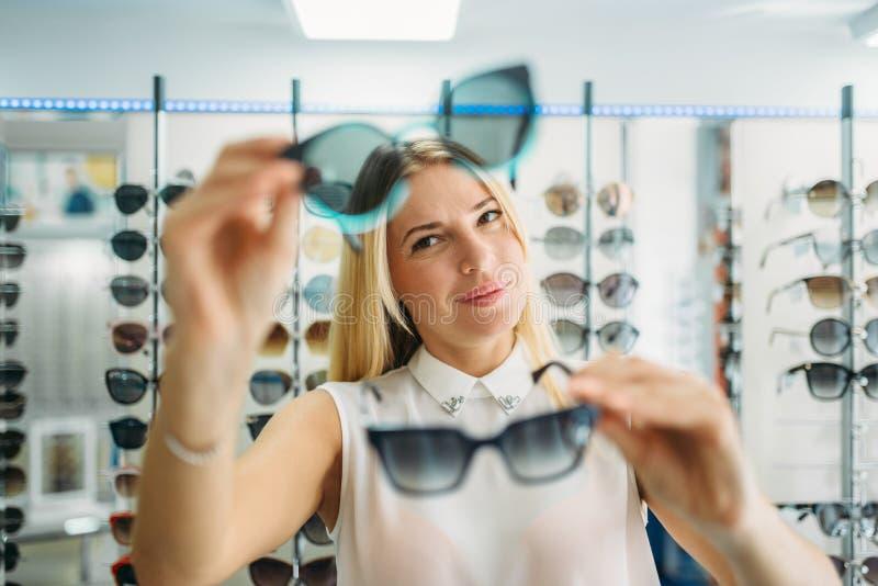 Женский покупатель выбирает солнечные очки в магазине оптики стоковые изображения rf