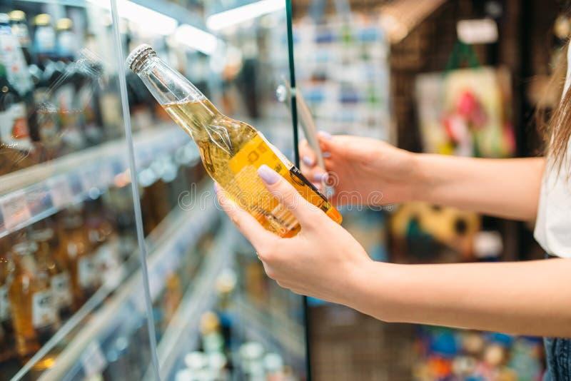 Женский покупатель выбирая пиво в супермаркете стоковое фото rf