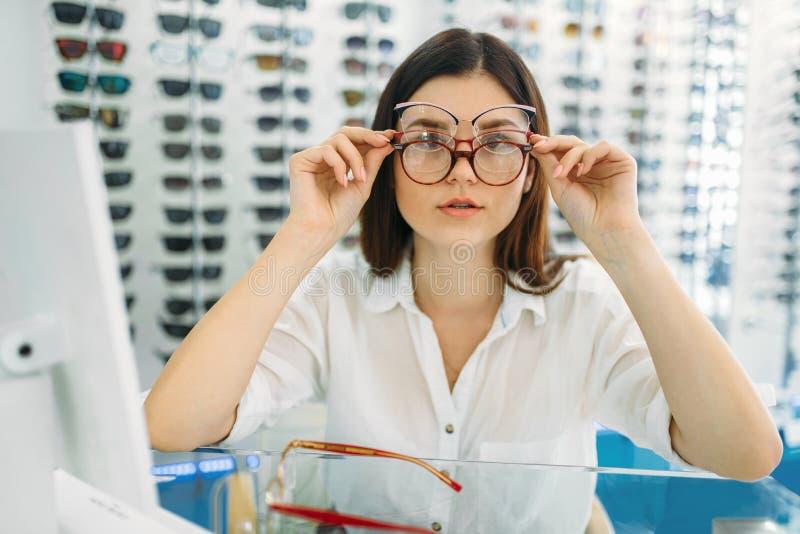 Женский покупатель пробует дальше много стекел в то же время стоковые фотографии rf