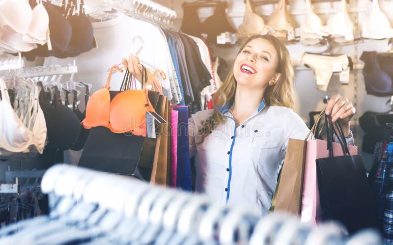 Женский покупатель похваляясь ее приобретения в магазине нижнего белья стоковая фотография rf
