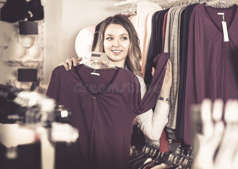 Женский покупатель рассматривая длинные рубашки рукава в нижнем белье ходит по магазинам стоковая фотография rf