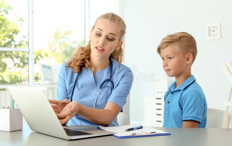 Женский помощник врача объясняя результат рассмотрения к ребенку в клинике стоковое изображение