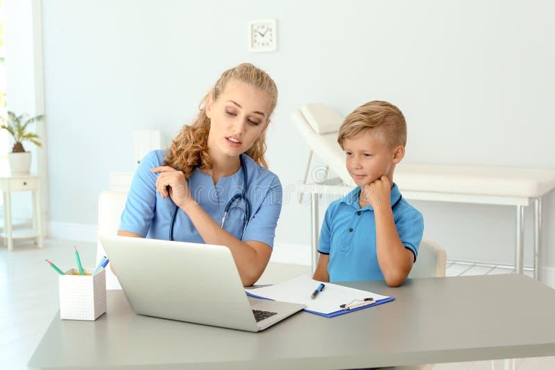 Женский помощник врача объясняя результат рассмотрения к ребенку в клинике стоковая фотография
