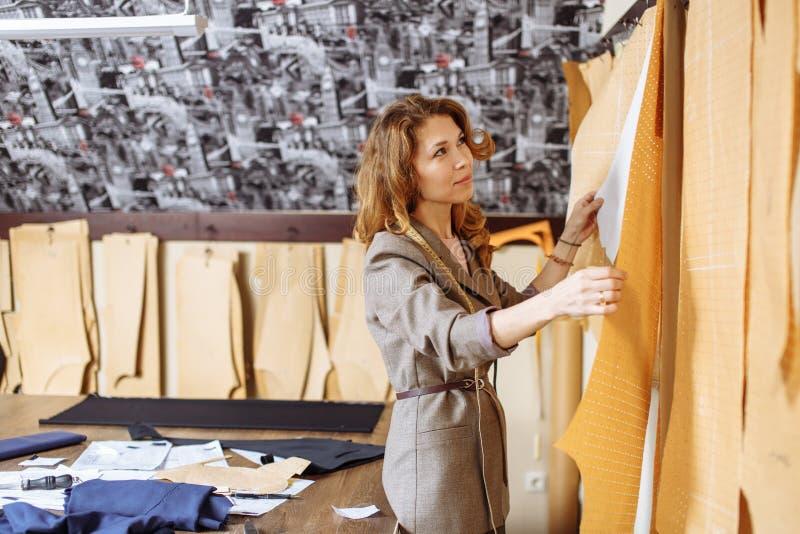 Женский портной выбирая картину бумаги одежды на мастерской snipper стоковые изображения rf