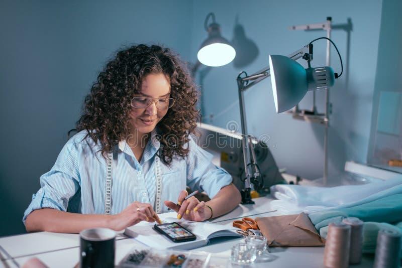 Женский портной выбирая модели для sewng от мобильного телефона стоковые фотографии rf