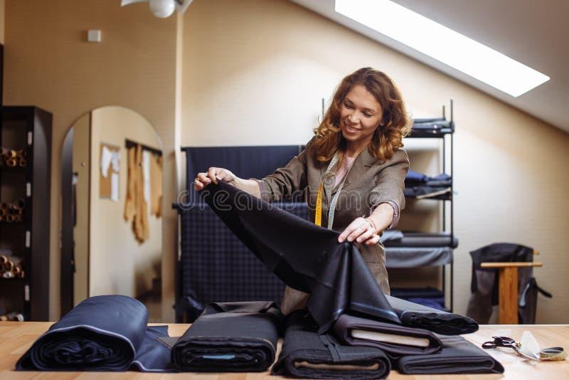 Женский портной выбирая ткань для вырезывания картины Индустрия носки людей, портняжничая отростчатую концепцию стоковые фото