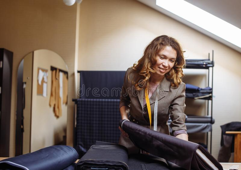 Женский портной выбирая ткань для вырезывания картины Индустрия носки людей, портняжничая отростчатую концепцию стоковое изображение