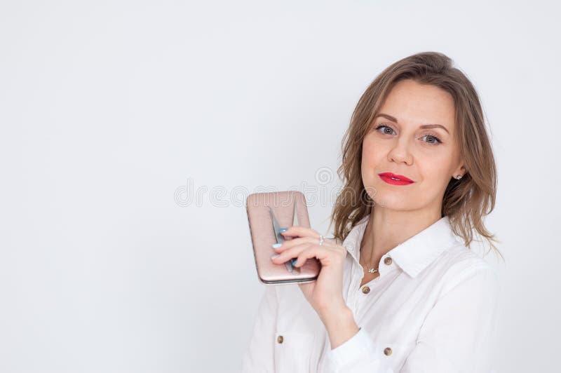 Женский портрет милого Cosmetician при светлые волосы и чувственные красные губы держа аппаратуры для маникюров в студии дальше стоковые изображения