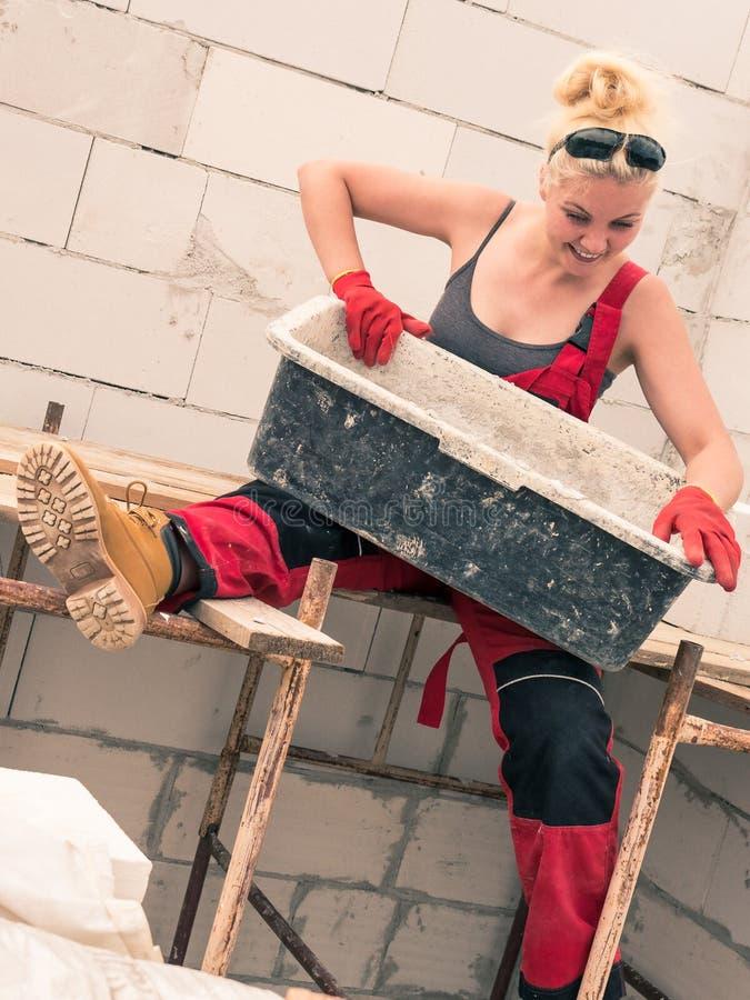 Женский построитель работая для построения нового дома стоковая фотография rf