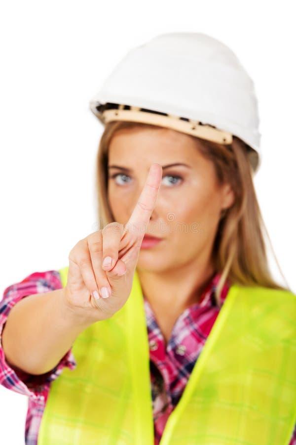 Женский построитель показывает один палец стоковые изображения rf