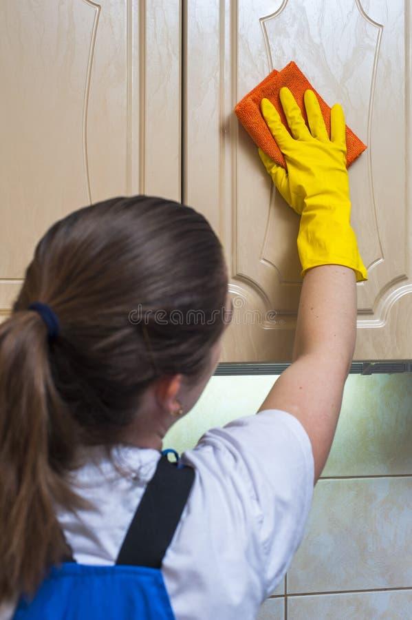 Женский привратник обтирая кухонный шкаф кухни с ветошью стоковая фотография