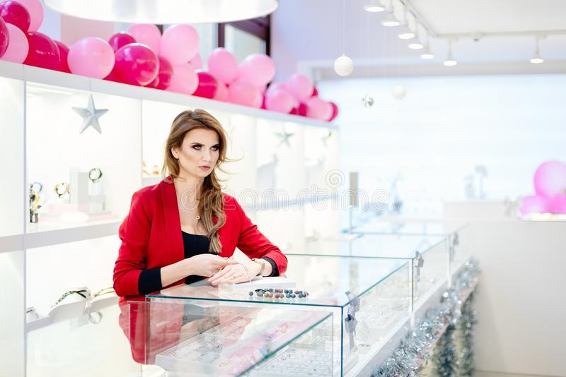 Женский продавец в роскошном ювелирном магазине представляет браслет стоковые изображения rf