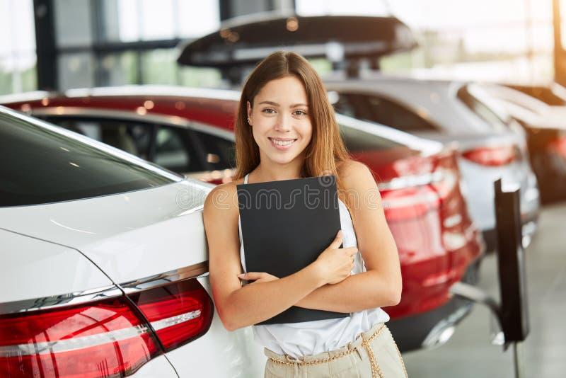 Женский продавец держа черную папку смотря камеру на автосалоне стоковая фотография