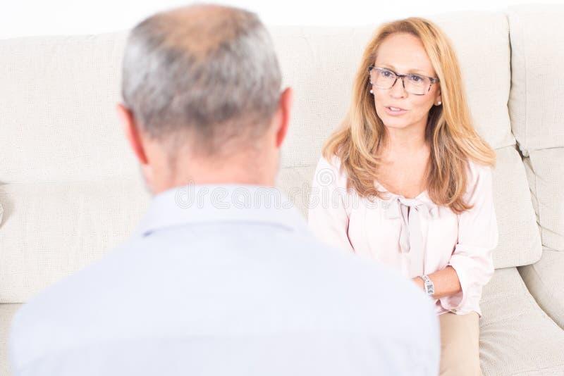 Женский психолог слушая к пожилому человеку стоковая фотография rf