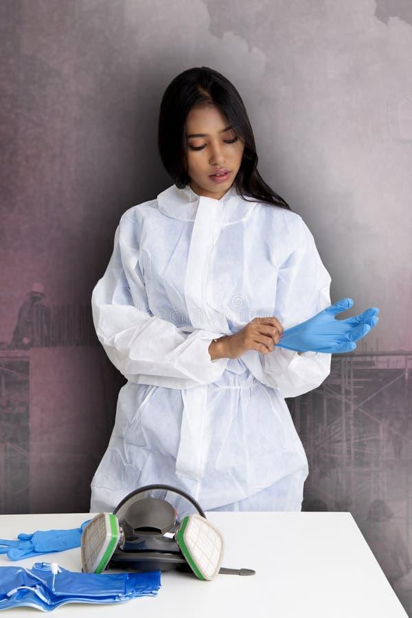 Женский работник в защитном костюме подготавливая работать стоковое фото rf