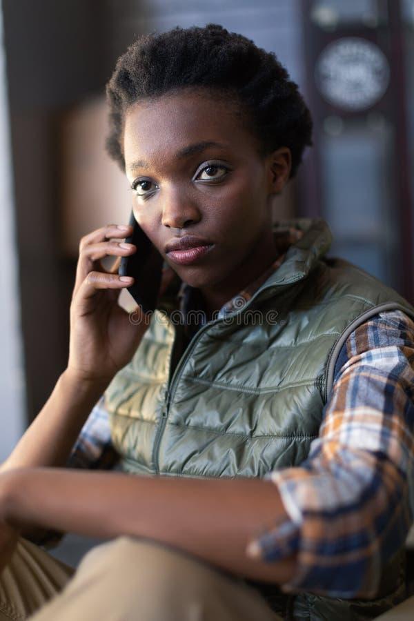 Женский работник говоря на мобильном телефоне в складе стоковая фотография rf