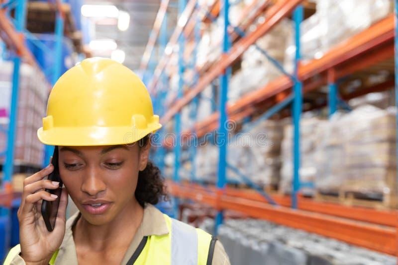 Женский работник говоря на мобильном телефоне в складе стоковое фото