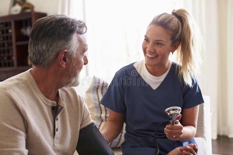 Женский работник здравоохранения делая домашнее посещение к старшему человеку, принимая его кровяное давление, конец вверх стоковая фотография rf