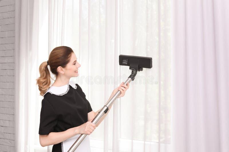Женский работник извлекая пыль от занавесов с профессиональным пылесосом, внутри помещения стоковые изображения