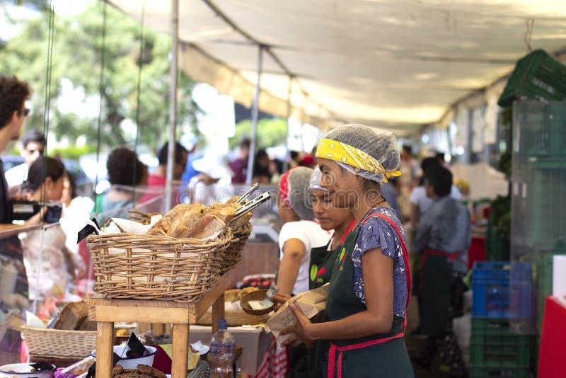 Женский работник на пекарне продавая хлеб стоковое фото