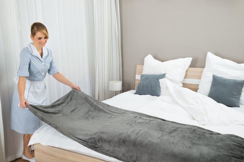 Женский работник домоустройства делая кровать стоковое фото rf
