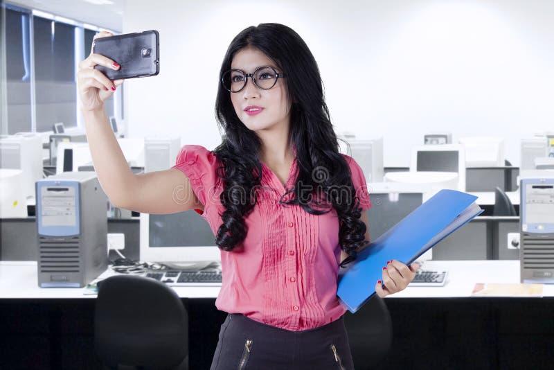 Женский работник принимая selfie в офисе стоковое фото