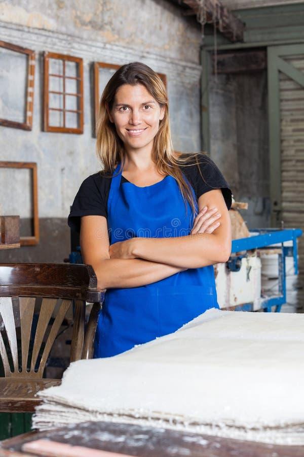 Женский работник с положением пересеченным оружиями в бумаге стоковое фото