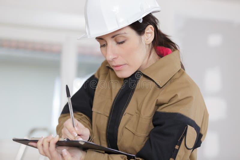 Женский рабочий-строитель принимая примечания на строительную площадку стоковые фотографии rf