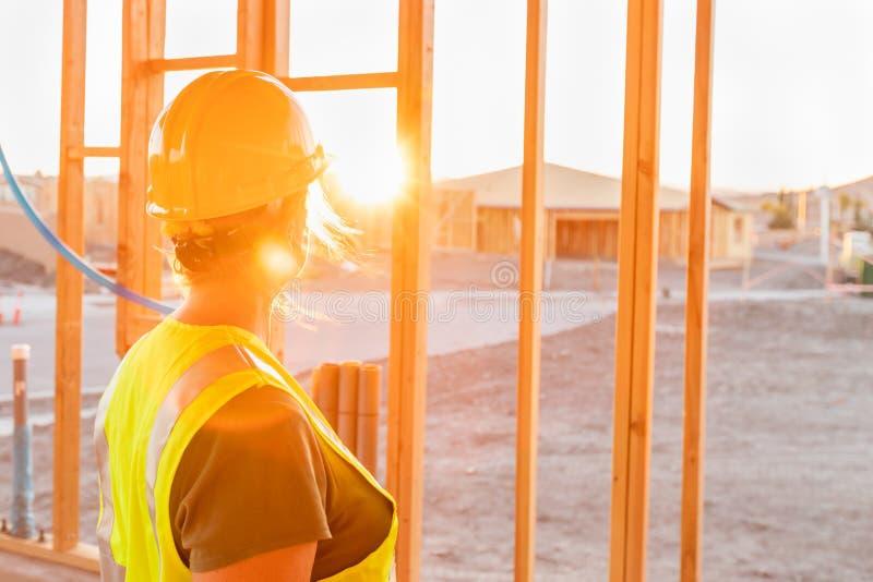 Женский рабочий-строитель смотря вне от новый домашний обрамлять стоковая фотография