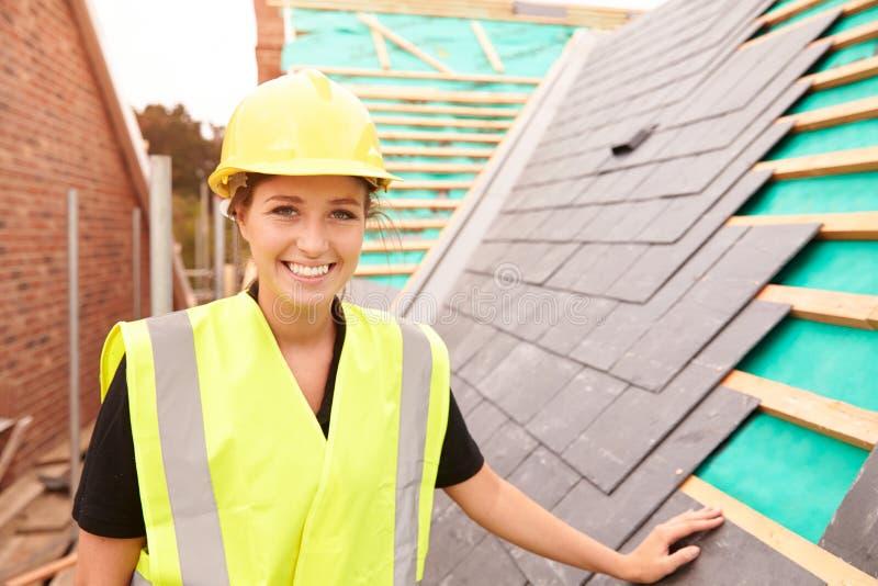Женский рабочий-строитель на месте кладя плитки шифера стоковые фото