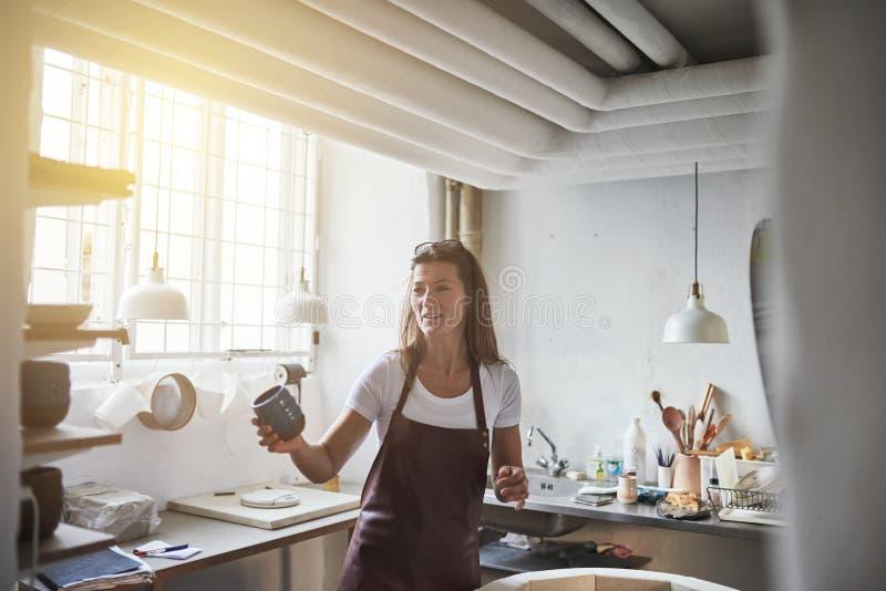 Женский ремесленник держа заново произвел гончарню в ее мастерской стоковое фото rf