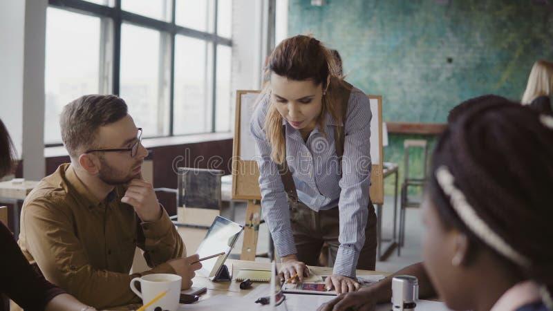Женский руководитель группы стоя близко таблица и давая направление к молодой творческой команде Метод мозгового штурма многонаци стоковое фото