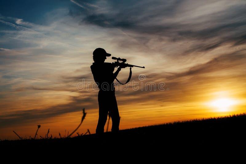 Женский силуэт охотника в заходе солнца стоковые фотографии rf