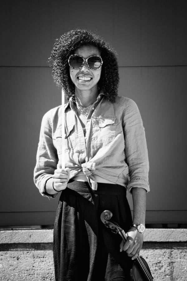 Женский скрипач держа аппаратуру и усмехаться стоковые фотографии rf