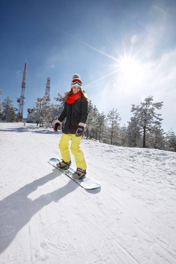 Женский сноубординг snowboarder в горе стоковое фото
