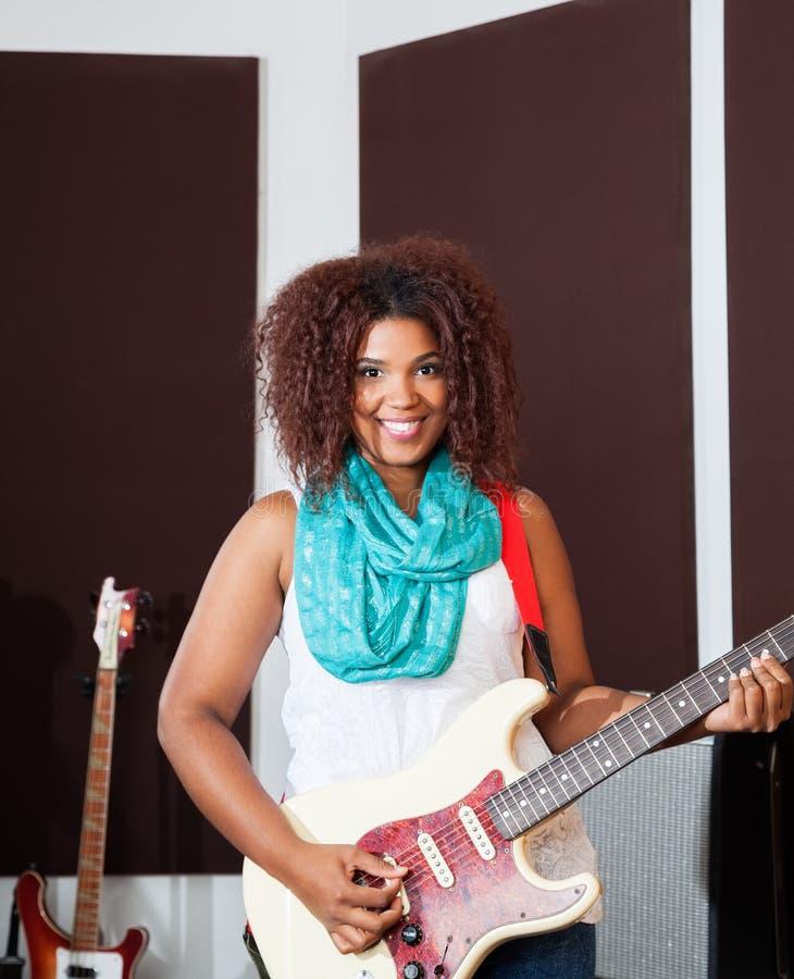 Женский совершитель играя гитару в студии стоковое фото rf
