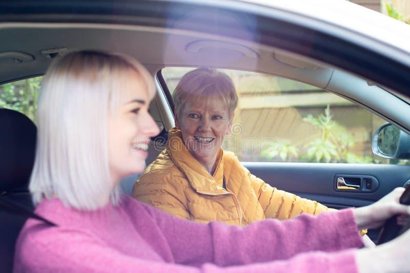 Женский сосед давая старший подъем женщины a в автомобиль стоковое фото rf