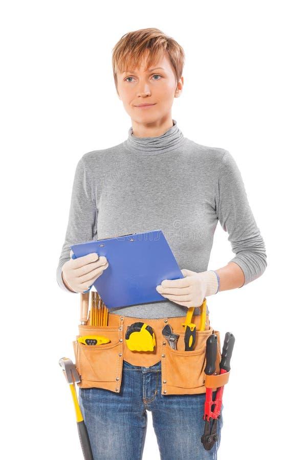 Женский строительный подрядчик с инструментами в поясе держа clipbo стоковое изображение rf